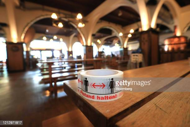 Spool of social distancing adhesive tape sits on a table inside a Bavarian-themed beer hall ahead of reopening in Berlin, Germany, on Thursday, May...