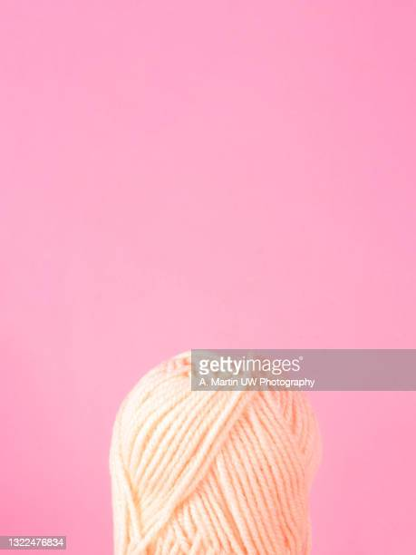 spool of yarn on pink background - wool stock pictures, royalty-free photos & images