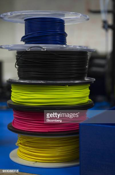 Spools of 3D printing filament sit stacked on a workstation at the Aleph Objects Inc LulzBot 3D printers production facility in Loveland Colorado US...