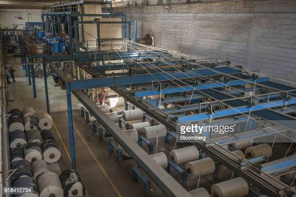 Spools of cotton rope move in to machines in the dying unit at the Artistic Denim Mills Ltd factory in Karachi Pakistan on Tuesday Feb 6 2018...
