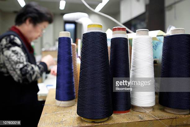 Spools of silk thread sit on a working table at the Milanorib Ltd manufacturing facility in Kiryu City Gunma Prefecture Japan on Monday Dec 13 2010...