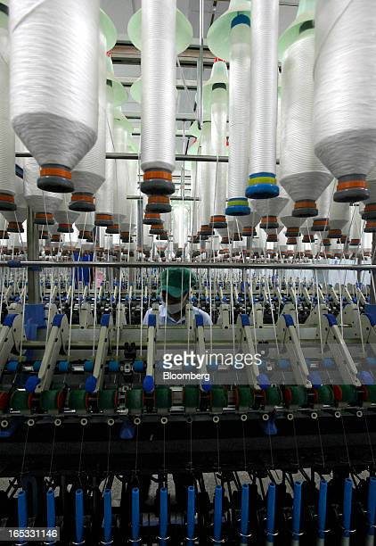 Spools of yarn run through spinning machines as a worker monitors operations in the spinning area at a PT Sri Rejeki Isman factory in Sukoharjo Java...