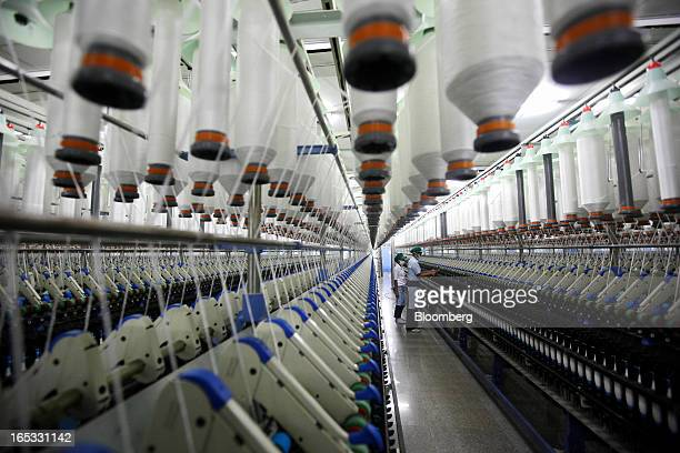 Spools of yarn run through spinning machines as workers monitor operations in the spinning area at a PT Sri Rejeki Isman factory in Sukoharjo Java...