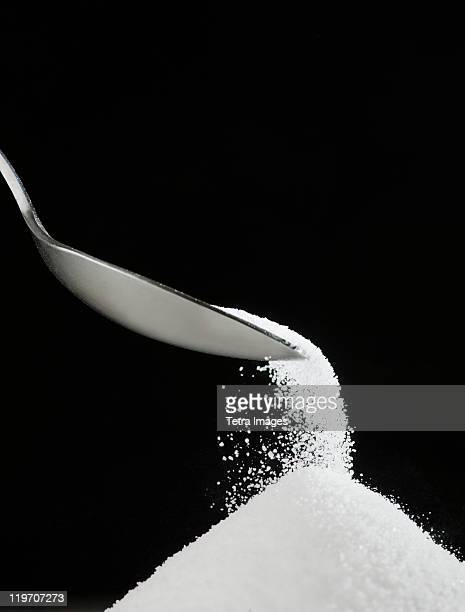 spoon and heap of sugar - sugar pile stock pictures, royalty-free photos & images
