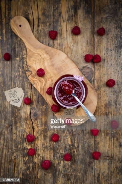 Spoon and jar of raspberry jam and raspberries on wood