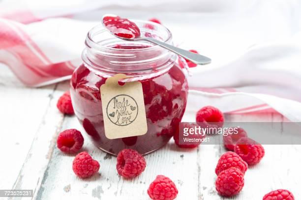 Spoon and jar of raspberry jam and raspberries