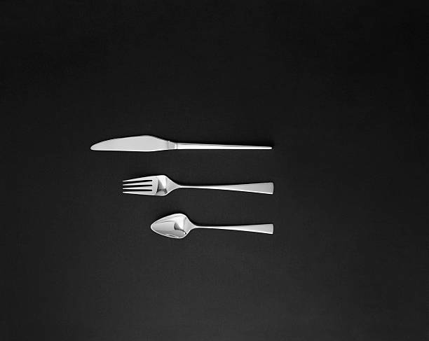 Spoon, fork and butter knife on black background
