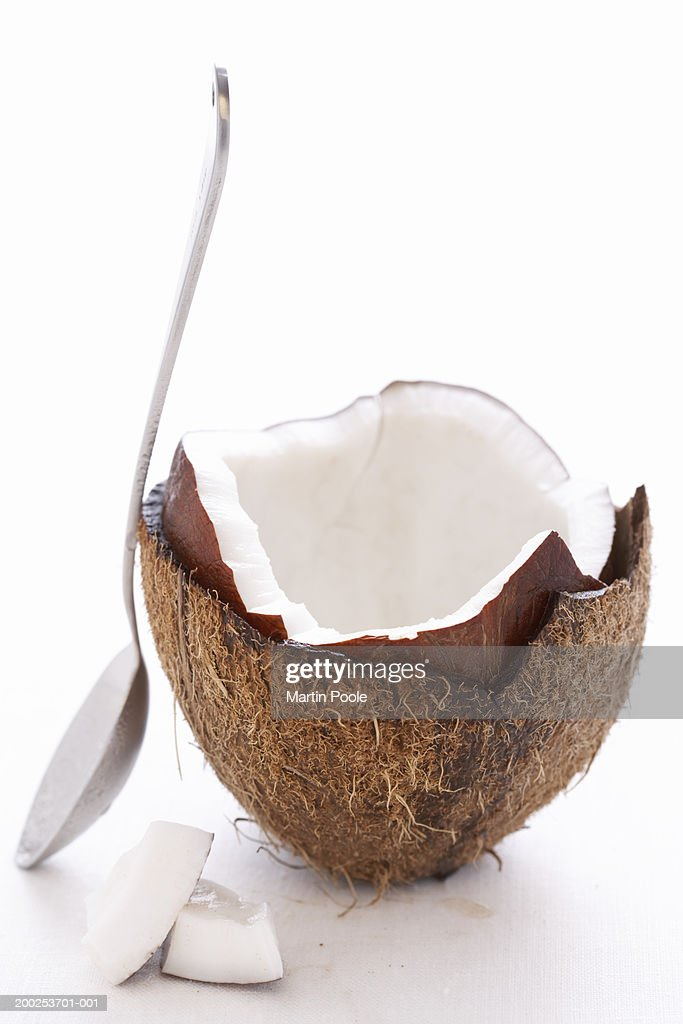 Spoon leaning on split coconut, close-up : Stock Photo