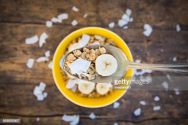 Spoon of granola, banana slice and coconut flakes
