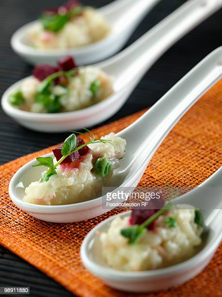Spoon of risotto with ham and pea.