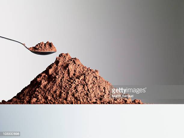 Spoon over heap of cocoa powder