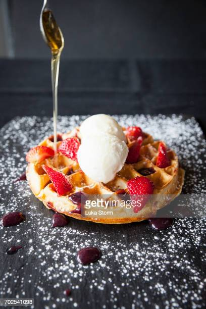 Spoon pouring maple syrup over strawberries and ice cream waffle on slate