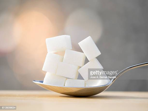 spoon with nine lumps of sugar equivalent to the content in sugar of a refreshing drink - excesso imagens e fotografias de stock