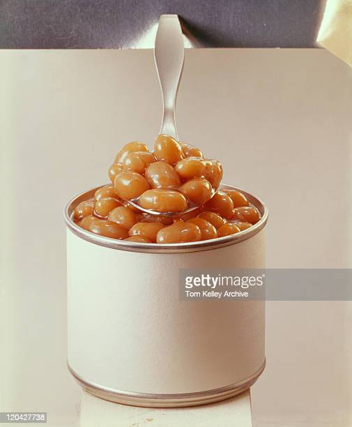 Spoonful of baked beans with tin can, close-up