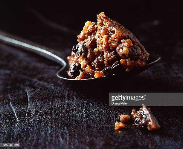 Spoonful of Christmas pudding on wooden surface