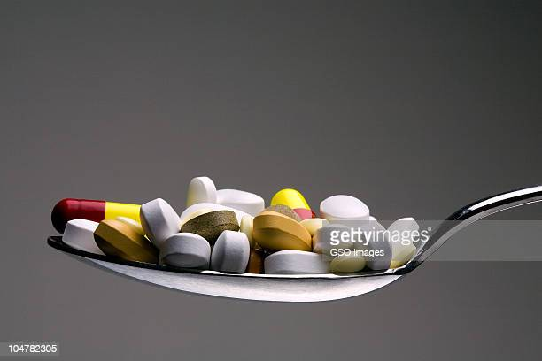 spoonful of medical tablets - hypochondria stock photos and pictures
