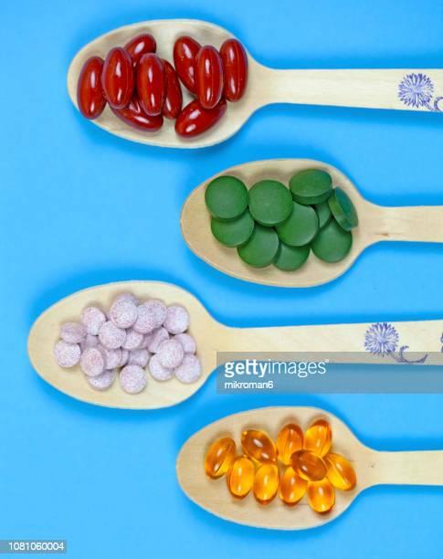 spoons full of medicine capsules and pills, medical concept - nahrungsergänzungsmittel stock-fotos und bilder