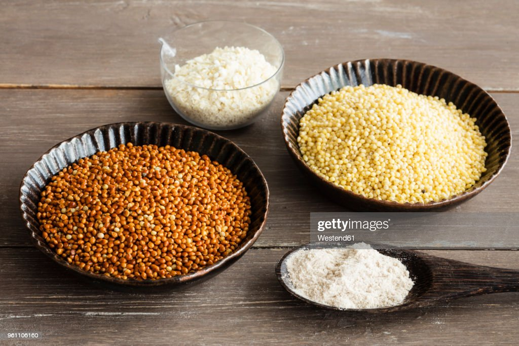 Spoons of Golden and brown millet, millet meal and millet flakes : Stock Photo