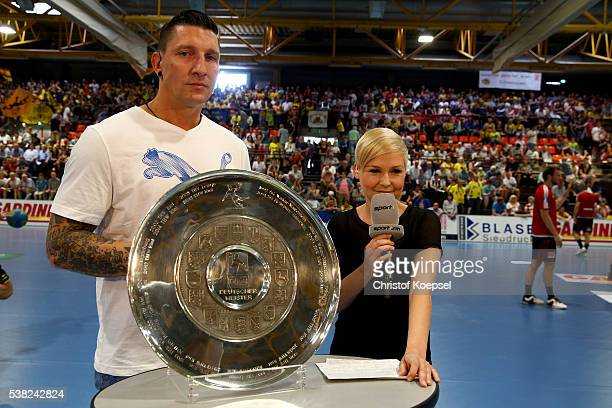 Sport 1 expert Stefan Kretzschmar and moderator Anett Sattler of Sport 1 pose with the German Championship lifts the German Championship trophy hy...