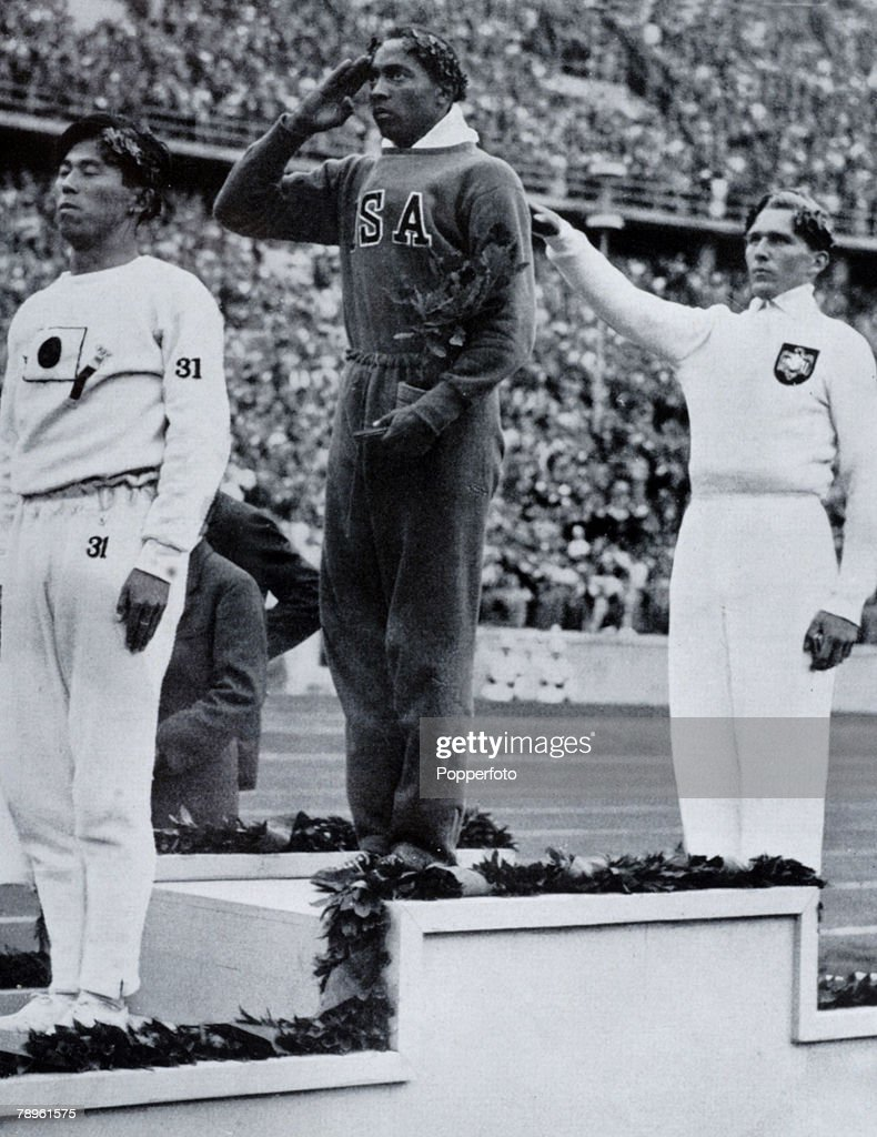 Sport, 1936 Olympic Games in Berlin, Mens Long Jump, Medal Ceremony, USA's Jesse Owens, centre, salutes the flag after winning the Gold medal, with left, Naoto Tajima, Japan (bronze medal), right, Luz Long, Germany,