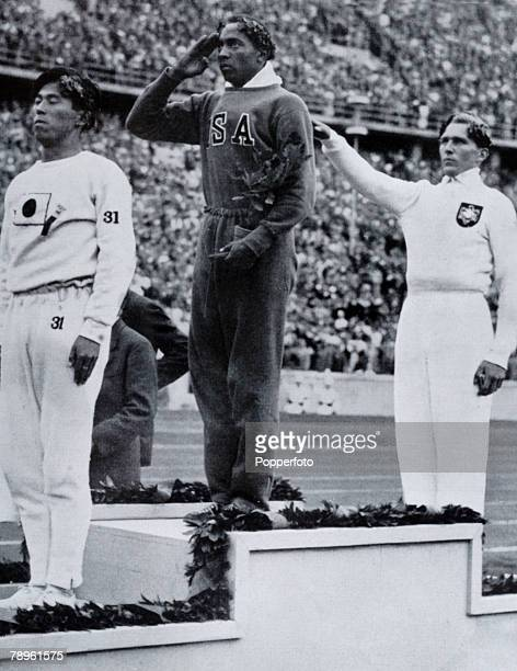 Sport 1936 Olympic Games in Berlin Mens Long Jump Medal Ceremony USA's Jesse Owens centre salutes the flag after winning the Gold medal with left...