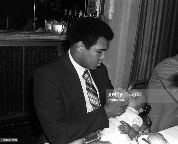 Sport Boxing London England 9th August 1977 Heavyweight boxing legend Muhammad Ali is pictured feeding his daughter Hana at a Press Conference Ali is...
