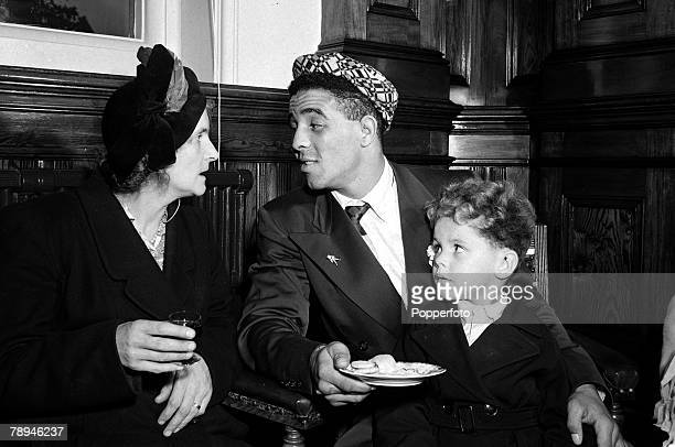 27th September 1951 Great Britain's Randolph Turpin with his 4 year old son Randolph Jnr chats to a guest at a civic reception at Leamington Spa...