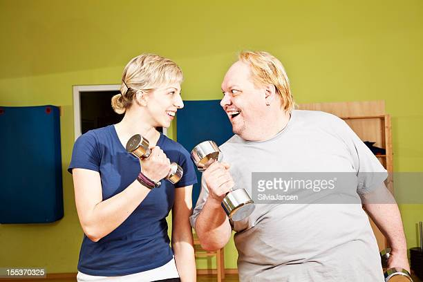 sport buddies exercising dumbbels with fun - skinny man fat woman stock pictures, royalty-free photos & images