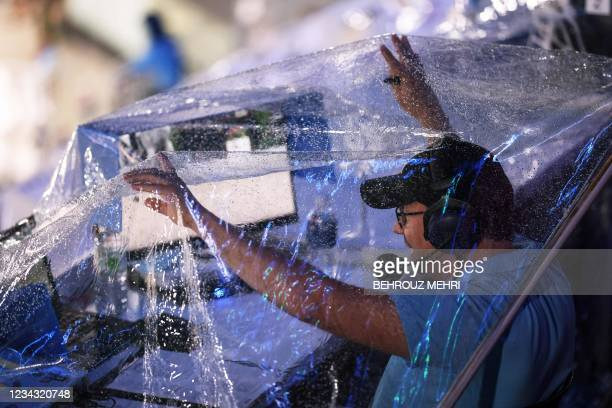 Sport commentator covers himself with a plastic sheet to protect from the rain in the equestrian's eventing individual dressage during the Tokyo 2020...