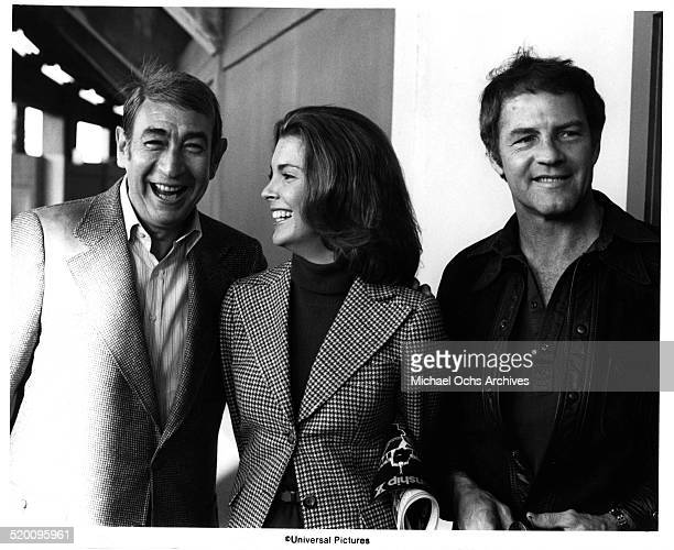 Sport commentators Howard Cosell and Frank Gifford walk with actress Marilyn Hassett on the set of TwoMinute Warning circa 1976 in Los Angeles...