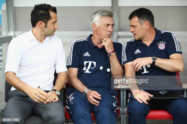 Sport director Hasan Salihamidzic head coach Carlo Ancelotti and assistant coach Willy Sagnol of Muenchen chat prior to a friendly match between...