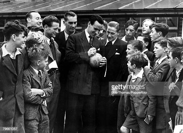 Sport, Football, 14th October 1949, After training, England's Neil Franklin is pictured signing a football watched by his team-mates Stan Mortensen,...