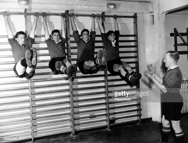 Sport Football 1957 The Manchester United Team exercises in the gym lifting their legs while hanging from the top rung of the wall bars LR David...
