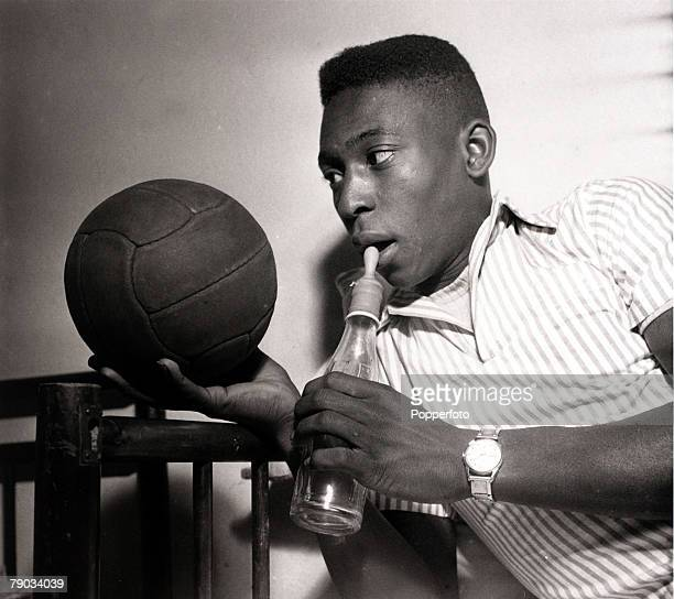 Sport Football circa 1959 A boyish looking Pele with the young Brazil star looking at a football and about to drink from a bottled topped by a teat...