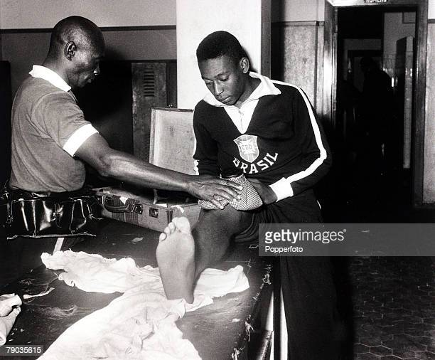 Sport Football circa 1959 Brazil's Pele receiving treatment on his knee from masseur / trainer Mario Americo who is wearing his trademark leather...