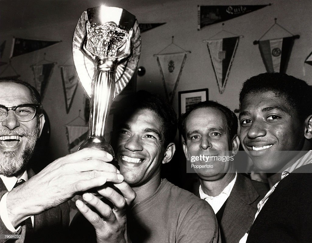 Sport. Football. June 1962. Brazil star Garrincha (second left) with the Jules Rimet World Cup trophy after Brazil's win in Chile in the 1962 tournament. He played 60 times for Brazil and with he and Pele in the team the national side never lost, his firs : News Photo