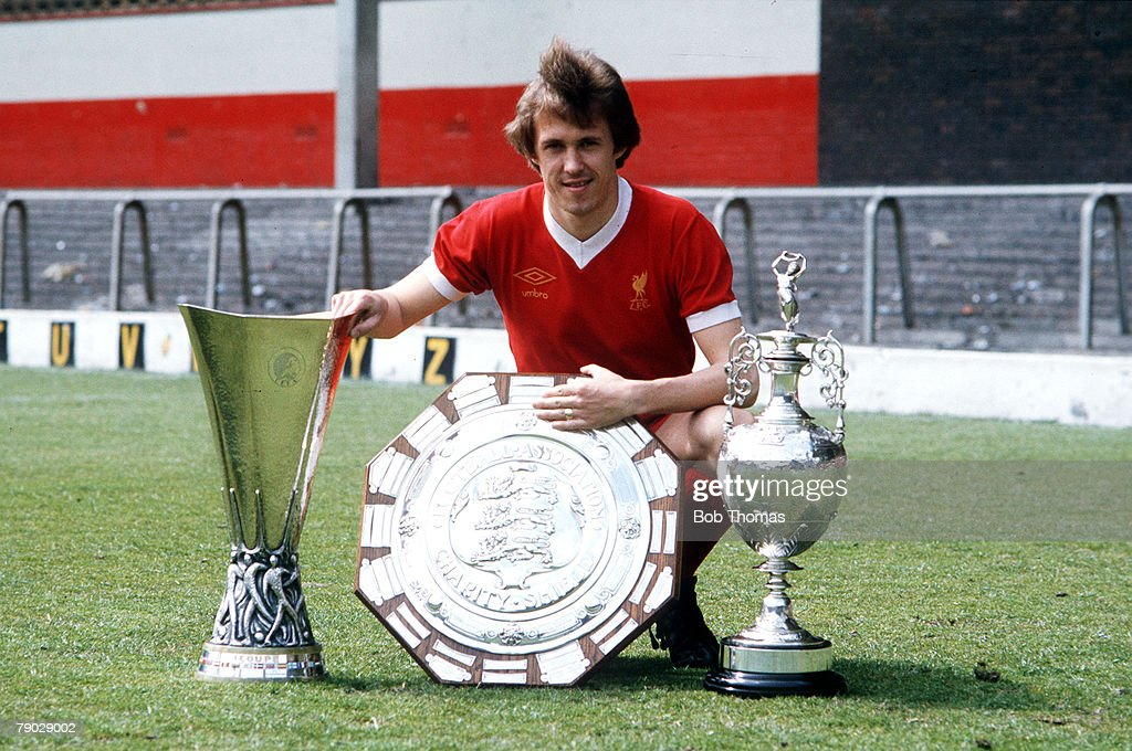 Sport, Football, 1976, Liverpool's Phil Neal is pictured with the L-R: UEFA Cup, Charity Shield, and League Championship trophies