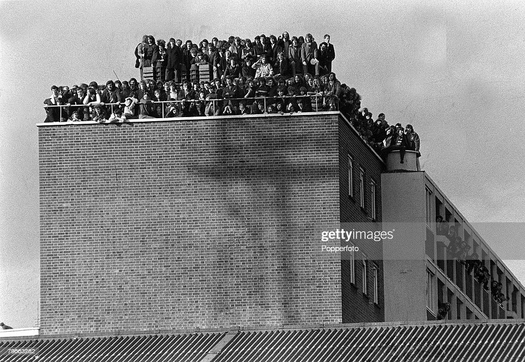 Sport, Football, London, England, 14th February 1972, Fans crowd the roof of a block of flats overlooking West Ham's Upton Park pitch as the Hammers win their FA Cup replay v Hereford 3-1