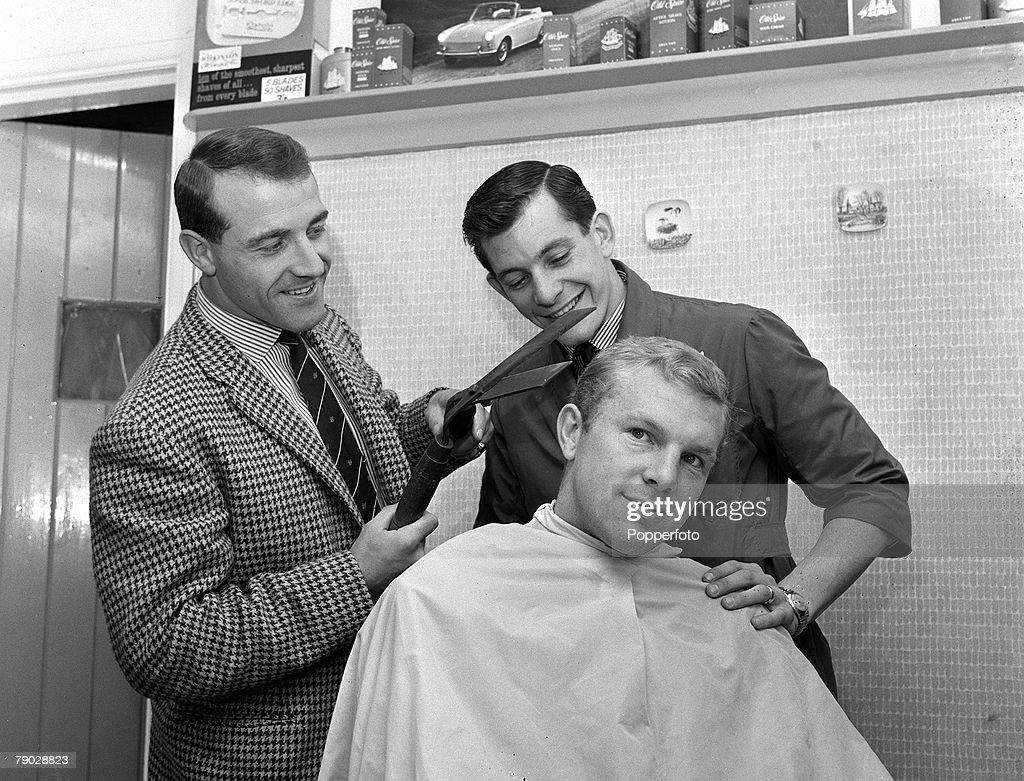 Sport. Football. London, England. 4th October 1962. England goalkeeper Ron Springett (left) attempts to cut his captain Bobby Moore's hair with shears, watched by a worried barber (centre). : News Photo