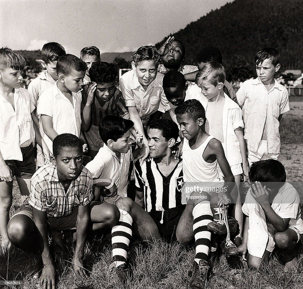 Sport. Football. November 1957. Botafogo and Brazil star Garrincha is pictured sitting with a group of local Brazilian children as he relaxes. : News Photo