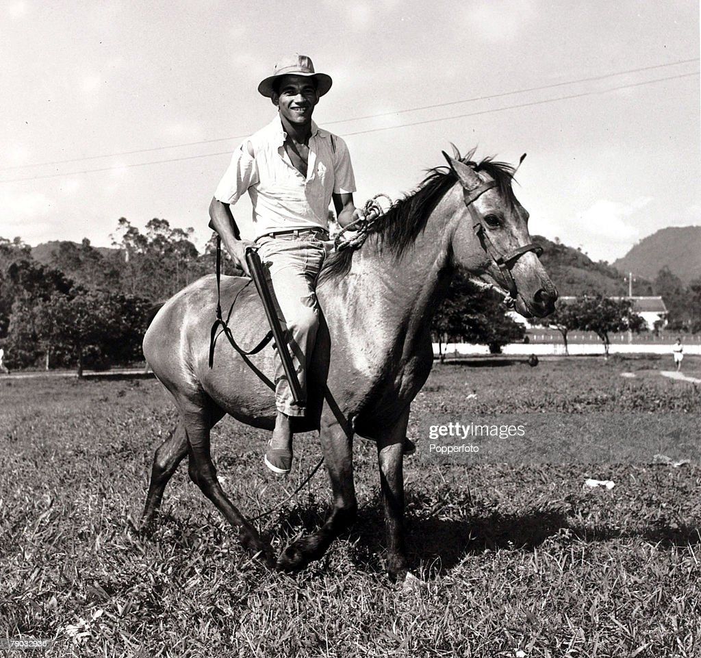 Sport. Football. November 1957. Brazilian star Garrinchais pictured riding a horse and carrying a shotgun in the Brazilian countryside. Garrincha was a double World Cup winner with Brazil in 1958 and 1962. : News Photo