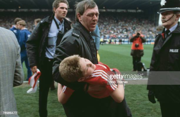 15th April 1989 FA Cup SemiFinal at Hillsborough Liverpool 0v Nottingham Forest 0 Match Abandoned An injured young boy is carried by a policeman