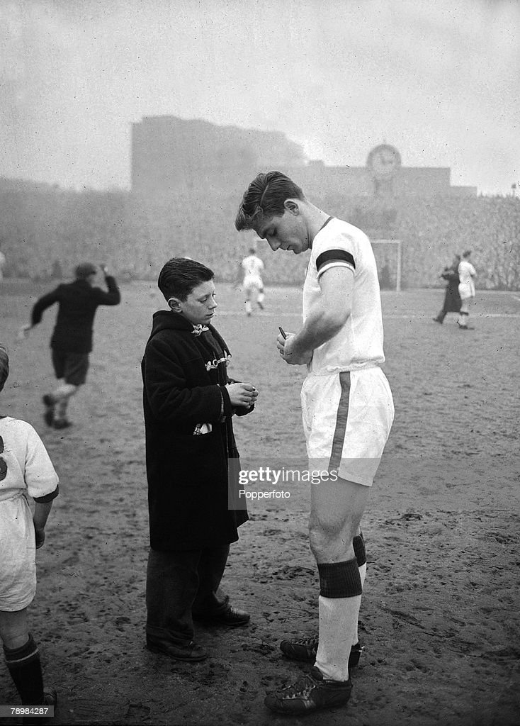 1st February 1958, Division 1, Arsenal 4, v Manchester United 5, at Highbury, Manchester United's Duncan Edwards signs an autograph for a young fan on the pitch just before the kick-off