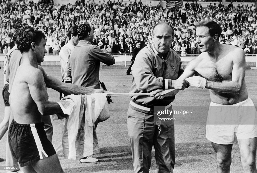 Sport. Football. pic: 23rd July 1966. 1966 World Cup Finals. World Cup Semi-Final. England 1 v Argentina 0. Wembley. England Manager Alf Ramsey, does his best to stop defender George Cohen, right, swapping shirts with Argentina's Alberto Gonzalez after wh : News Photo