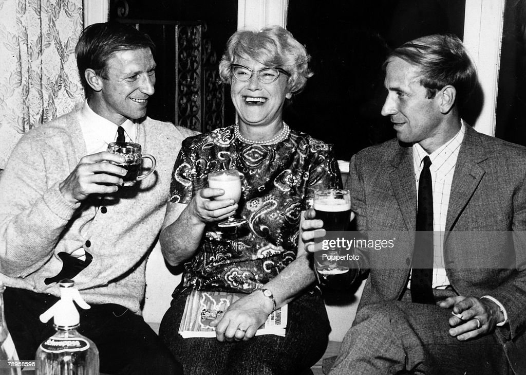Sport. Football. pic: 28th July 1966. England internationals Jack, left, and Bobby Charlton enjoy a celebration drink with their mother Cissie after the World Cup Semi-Final win over Portugal at Wembley. : News Photo