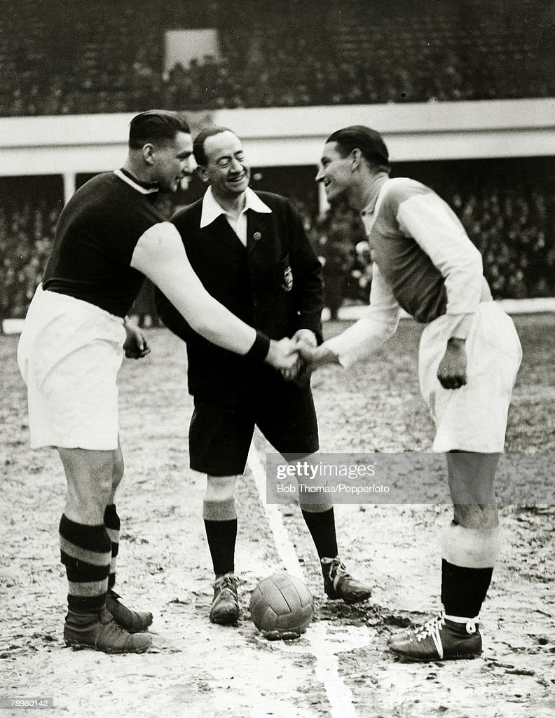 Sport. Football. pic: 2nd December 1935. West Ham United v FC.Austria in a European Friendly Match. On a frosty Upton Park, West Ham United captain Jim Barrett, left, meets the FC.Austria captain Nausch, as referee WJ.Lewington looks on. : News Photo