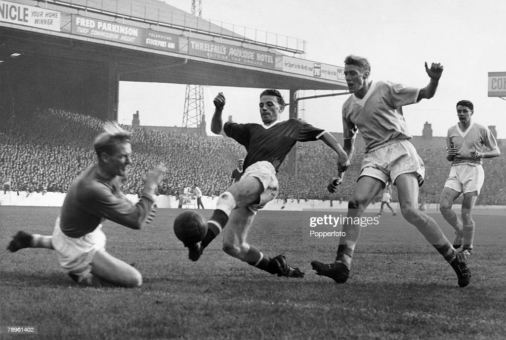 circa 1958, Division 1, Manchester City v Manchester United at Maine Road, Manchester United's Albert Scanlon opposed by Manchester City's goalkeeper Bert Trautmann, left and defender Cliff Sear, right