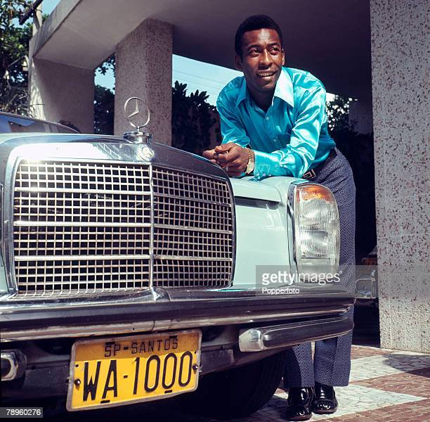 circa 1966 Pele the Santos and Brazil star wearing fashionable silk shirt and to show the trappings of success posing with a Mercedes car