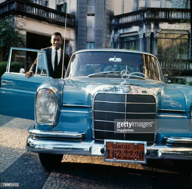 circa 1966 Pele the Santos and Brazil star wearing a smart suit and to show the trappings of his success posing with a Mercedes car