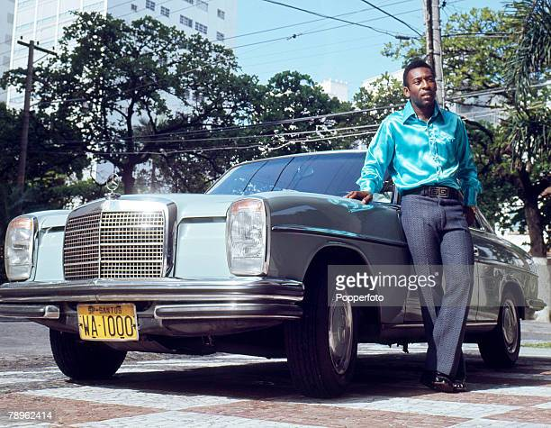 circa 1966 Pele the Santos and Brazil star wearing a stylish silk shirt and to show the trappings of his success posing with a Mercedes car